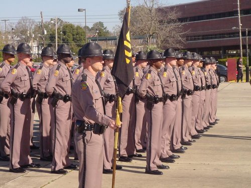 Robert Crouch holding the flag for the 100th graduating class of the Florida Highway Patrol